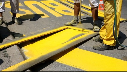 Hand spraying of bus station sign at a street