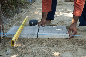 Worker puts sidewalk tiles