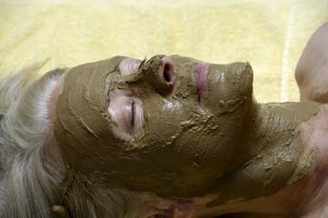 Ältere Frau mit Gesichtsmaske aus Heilerde