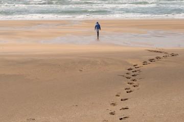 Fußspuren im Sand und Person am Sandstrand in Island