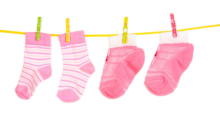 pink baby socks on rope isolated on white