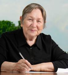Portrait of  senior woman  writing