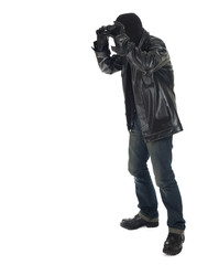 thief in black clothes and balaclava using binoculars