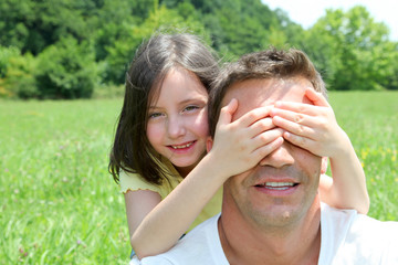 Young girl hiding her father's eyes