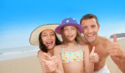 Parents with girl showing thumbs up