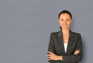 Businesswoman standing on grey background with arms crossed