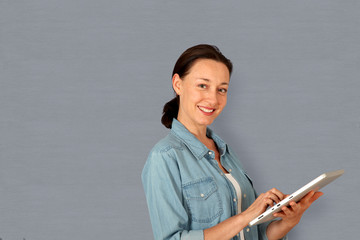 Smiling woman using electronic tablet