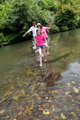 Family crossing river barefoot