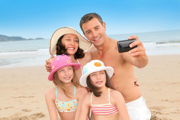 Family taking picture of themselves at the beach