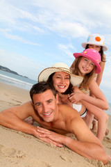 Portrait of family laying down sandy beach