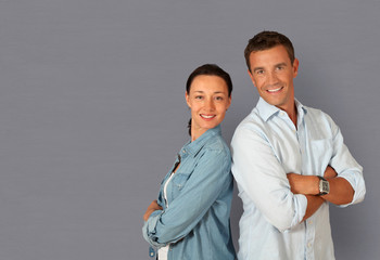 Couple standing on grey background with arms crossed