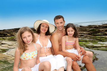 Happy family of 4 people sitting at the beach