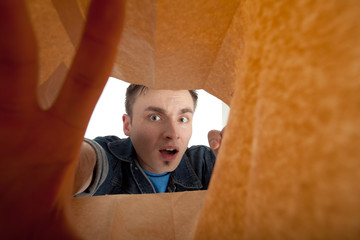 frightened young man looking to paper bag