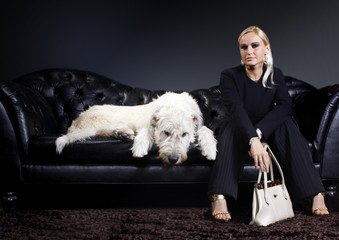 junge Frau mit Hund auf Ledersofa