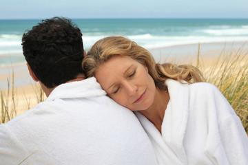 Couple in bathrobe at the beach