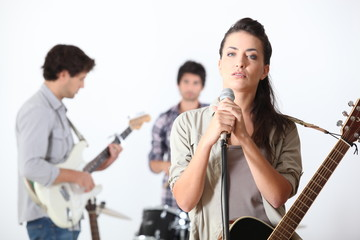 a guitar player, a drummer and a female singer