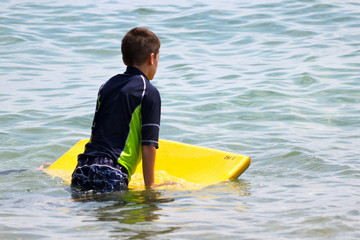 Boy at Ocean with Boogie Board