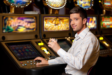 young handsome man next to slot machine