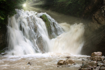 Beautiful waterfall in mountains and a rays of light