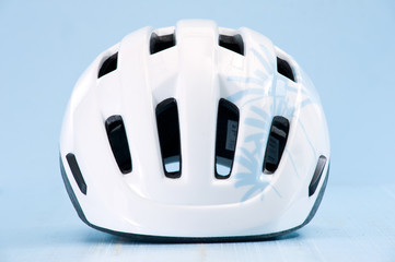 White bike helmet isolated on blue background. Front view.