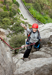 Cheerful female climber ascending a rock