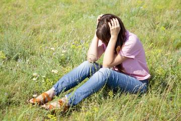 Sad girl at green grass at countryside.