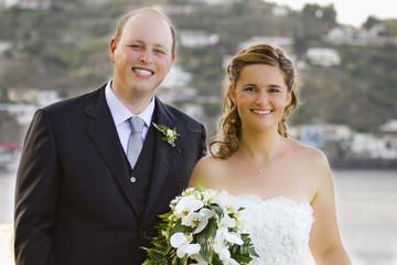 Sposini che sorridono con il bouquet
