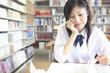 図書室で本を開く女子高校生