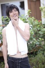 タオルを首にかけ微笑む男性