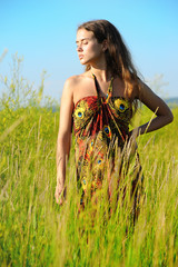 girl in colorful sun-dress in grass