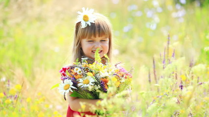Beautiful girl with flowers in the meadow