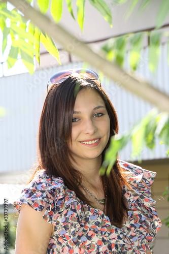 junge Frau mit braunem Haar im Sommerkleid und Brille