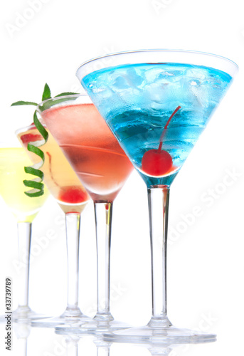 Martini alcohol cocktails in row  blue hawaiian, tequila sunrise