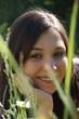 junge Frau versteckt sich hinter Grashalmen und Magaritten