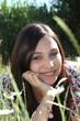 junge Frau liegt zwischen Magaritten im Garten und ist verliebt