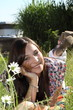 junge Frau liegt zwischen Blumen auf der Wiese und lacht
