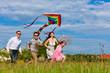 Glückliche Familie läuft auf einer Wiese mit Drachen