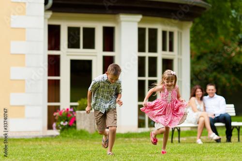 Familie sitzt und spielt vor ihrem Eigenheim