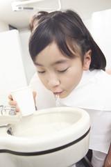 歯科治療後にうがいをする子供