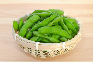 Boiled green soybeans in a small bamboo basket