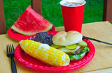Summer picnic with sweetcorn, hamburger and watermelon