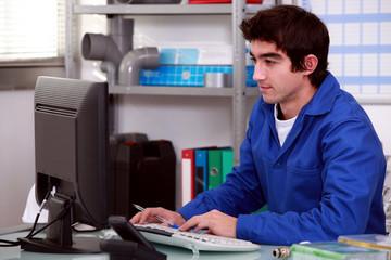 Plumber using desktop computer