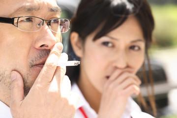 タバコを吸うビジネスマンと嫌がるオフィスレディ