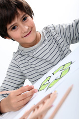 little boy drawing a circle composed of arrows