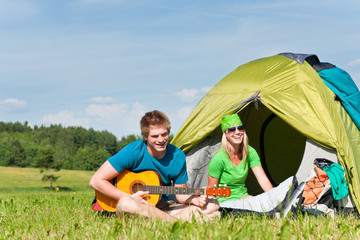 Camping couple playing guitar by tent countryside