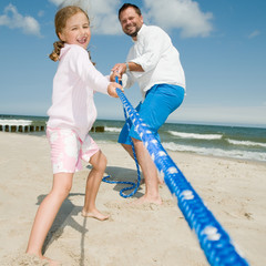Tug-of-war - girl with father playing on the beach