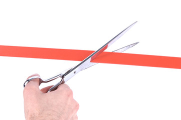 Closeup of a mans hand cutting a red ribbon with scissors