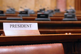 empty president seat in conference hall poster