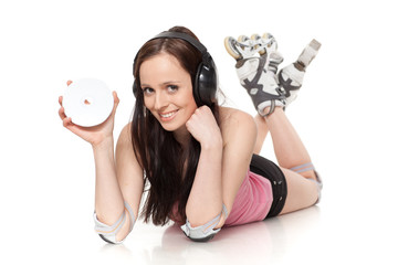 Young woman in rollerskates with earphones and a compact disc.