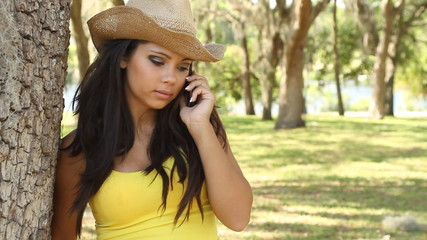 Pretty young woman in cowboy hat talking on mobile phone